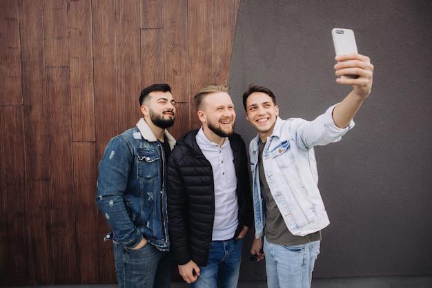 Felizes amigos tomando uma selfie ao lado da parede