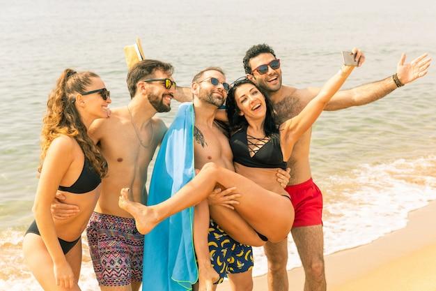 Felizes amigos tomando uma selfie na praia de barcelona