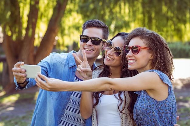 Felizes amigos tomando uma selfie no parque