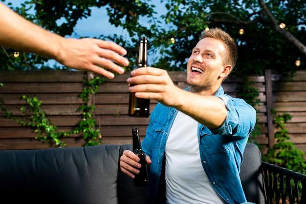 Felizes amigos trocando cervejas