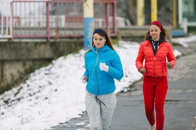 Felizes atletas do sexo feminino correndo na estrada no inverno