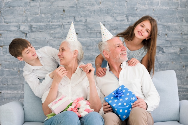 Felizes avós olhando seus netos aproveitando a festa de aniversário