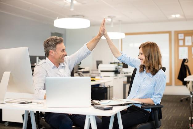 Felizes colegas de trabalho dando mais cinco uns aos outros