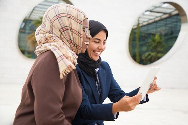 Felizes colegas femininas usando tablet para vídeo chamada