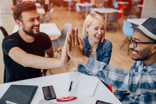 Felizes colegas modernos dando mais cinco