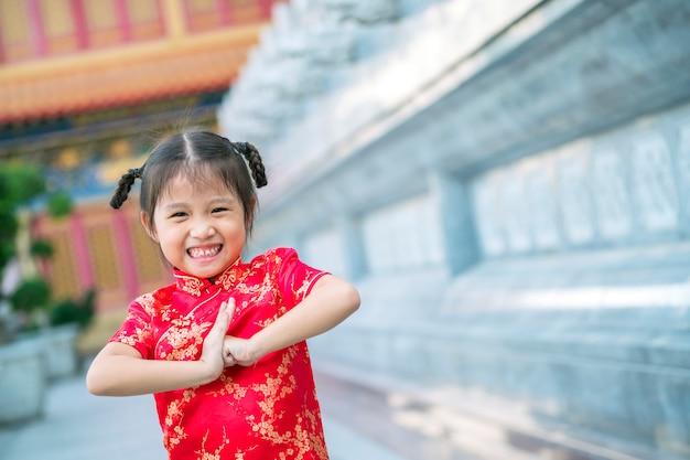 Felizes crianças asiáticas com vestido vermelho chinês no templo chinês
