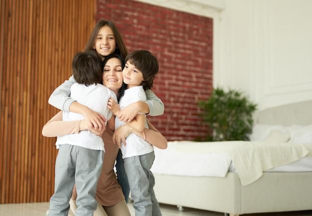 Felizes crianças latinas, adolescente e dois meninos gêmeos abraçando a mãe enquanto se divertem juntos dentro de casa. mãe brincando com seus filhos em casa. família, conceito de paternidade