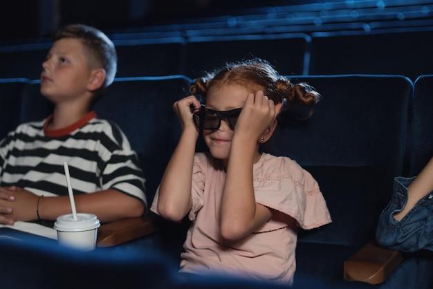 Felizes crianças pequenas com óculos 3d no cinema, assistindo ao filme.