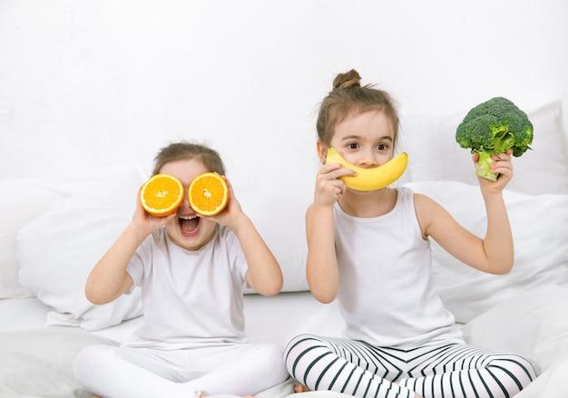 Felizes, dois filhos bonitos brincam com frutas e vegetais. alimentação saudável para crianças.