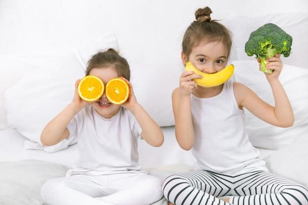 Felizes dois filhos bonitos brincam com frutas e vegetais na cama. alimentação saudável para crianças.
