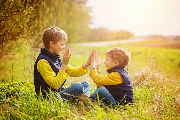 Felizes dois irmãos do litte que têm o divertimento junto no tempo do dia ensolarado.
