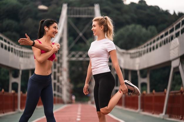 Felizes duas atraentes jovens esportistas em pé ao ar livre fazendo treinamento esportivo ao ar livre enquanto conversam
