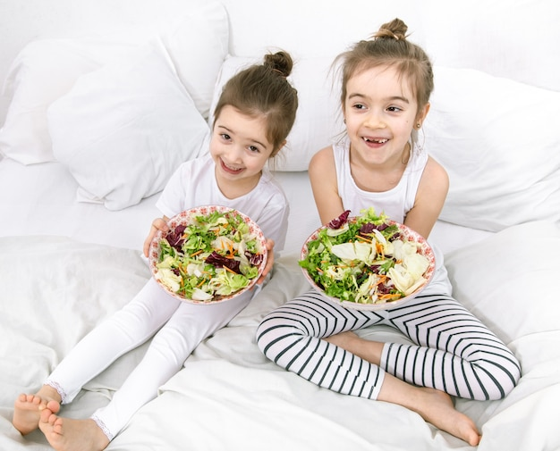 Felizes duas crianças fofas comendo salada de legumes no quarto na cama. alimentação saudável para crianças e adolescentes.