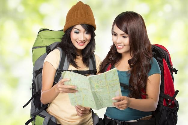 Felizes duas mulheres jovens saindo de férias com mochila e mapa
