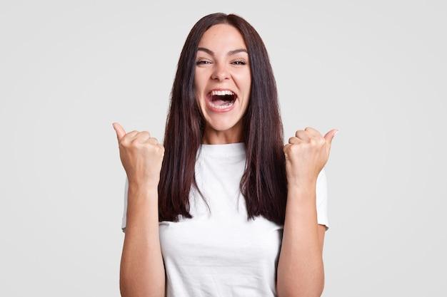 Felizes e felizes mulheres morenas apertam os punhos em triunfo, descobrem sobre a gravidez, vão compartilhar esta maravilhosa notícia com o marido, vestido com roupa branca. conceito de pessoas e conquista