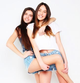 Felizes e sorridentes lindas adolescentes ou amigas se abraçando sobre o branco