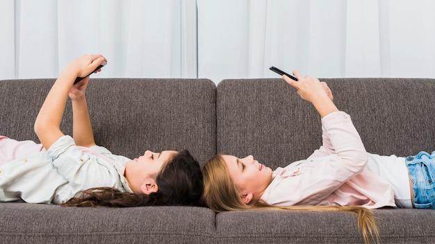 Felizes femininos amigos deitado no sofá usando telefone inteligente