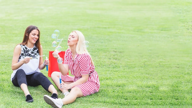 Felizes femininos amigos desfrutando de soprar bolhas no parque
