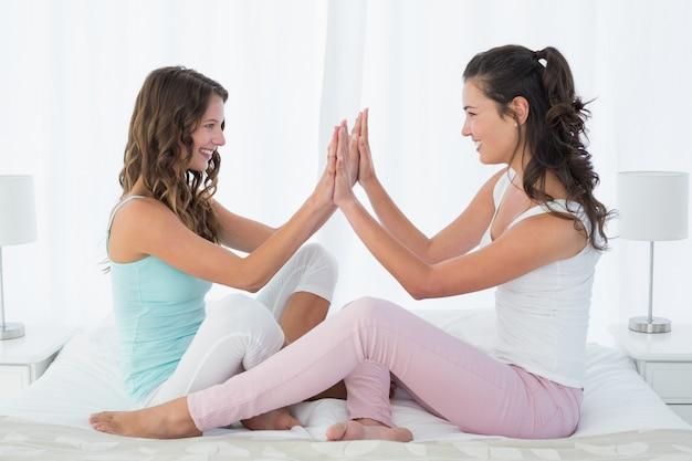 Felizes femininos amigos jogando o jogo de palmas na cama