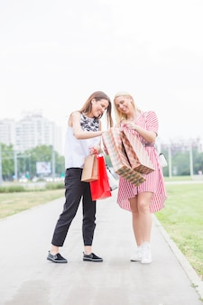 Felizes femininos amigos olhando nos sacos de compras