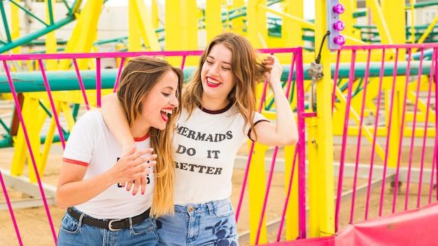 Felizes femininos amigos se divertindo no parque de diversões