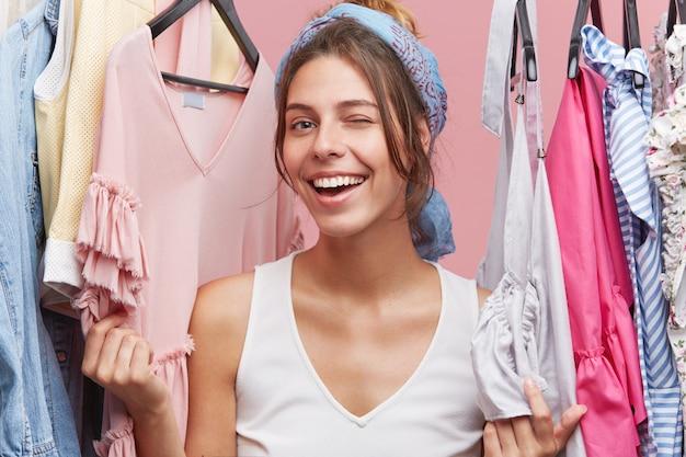 Felizes femininos olhos piscando em pé perto de prateleiras com roupas, se divertindo e emoções positivas após compras bem sucedidas.
