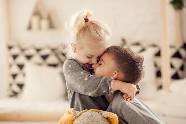 Felizes filhos bonitos irmão e irmã no berçário brincar e rir, infância feliz