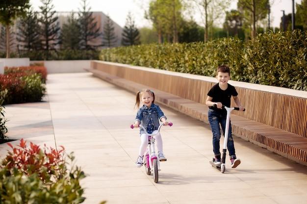 Felizes filhos fofos, um menino e uma menina andam de bicicleta e uma scooter no parque na primavera