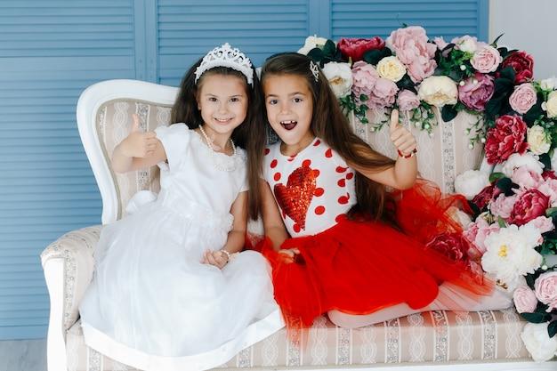 Felizes garotas bonitas posando no sofá e mostrando os polegares para cima