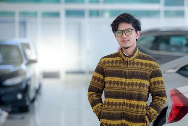 Felizes homens asiáticos que compram carros novos em salas de exposição e clientes satisfeitos acabam de comprar carros em concessionárias.