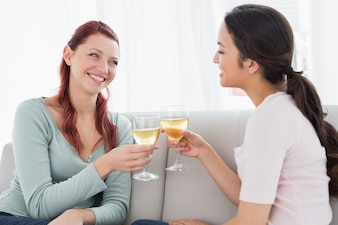 Felizes jovens amigas brindando com taças de vinho em casa