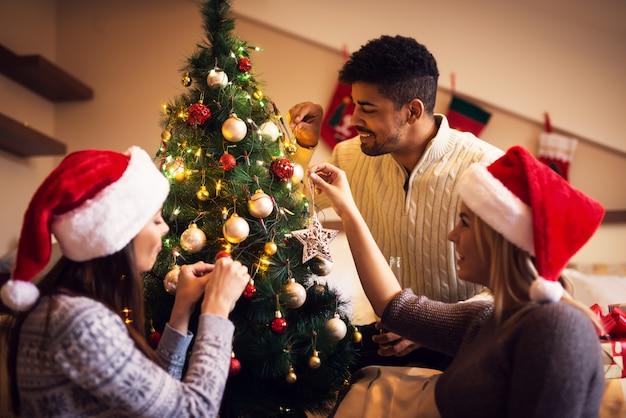 Felizes jovens amigos felizes estão decorando a árvore de natal.