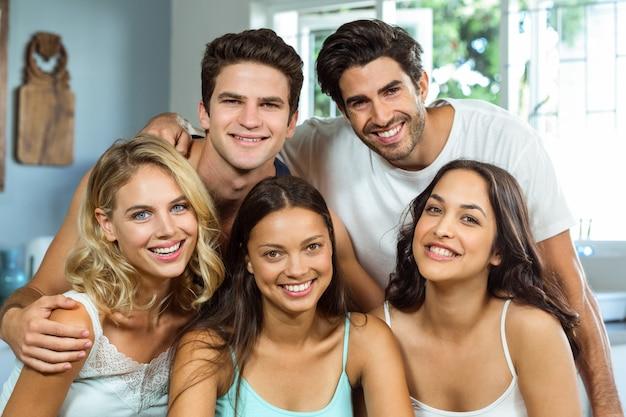 Felizes jovens amigos masculinos e femininos em casa