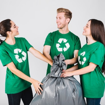 Felizes jovens amigos segurando o saco de lixo
