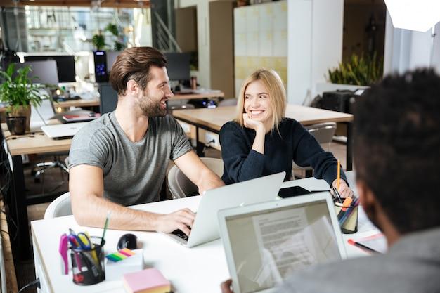 Felizes jovens colegas sentados no escritório de coworking