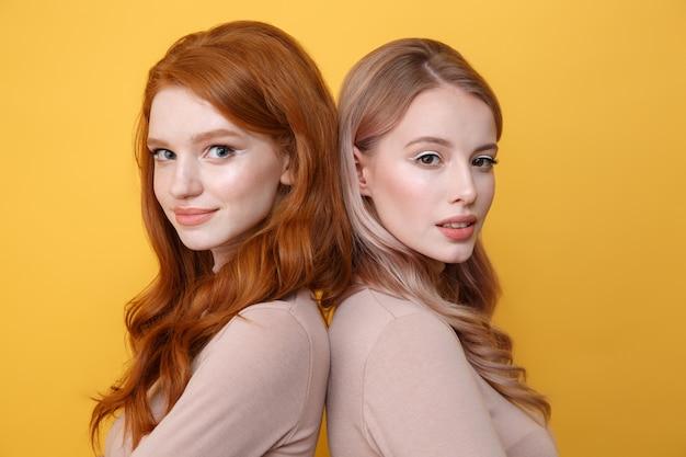 Felizes jovens duas senhoras em cima de parede amarela