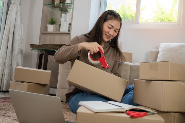 Felizes jovens empreendedores asiáticos usando dispensador de fita adesiva para fechar a embalagem de entrega de produtos aos clientes.