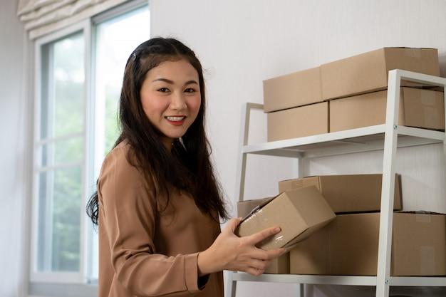 Felizes jovens empresários asiáticos estão organizando caixas para entregar produtos aos clientes.
