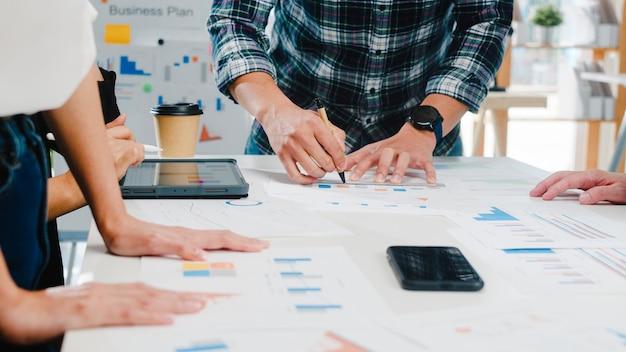 Felizes jovens empresários e empresárias da ásia reunindo-se para debater idéias sobre novos colegas de projeto de papelada trabalhando juntos, planejando uma estratégia de sucesso, e desfrutar do trabalho em equipe em um pequeno escritório moderno.