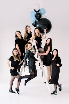 Felizes jovens sete garotas de vestido preto se divertindo comemorando aniversário na sala de luz. os amigos se divertindo posando na escada, decorada com balões de ar coloridos.