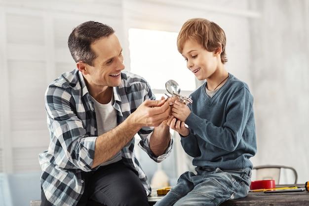 Felizes juntos. homem bonito e sorridente de cabelos escuros mostrando instrumentos para o filho enquanto está sentado na mesa e o filho dele sentado perto dele