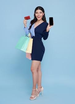 Felizes lindas mulheres asiáticas mostrando cartão de crédito e smartphone e segurando sacolas de compras isoladas sobre fundo azul.