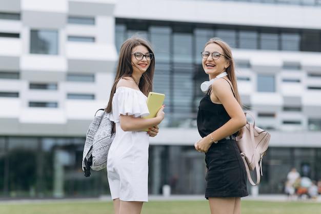 Felizes melhores amigas abraçando e posando em um parque. dois estudantes posando olhando para você ao ar livre em um campus universitário