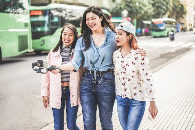 Felizes meninas asiáticas fazendo vídeo vlog na estação de ônibus. amigos da moda blogando nas redes sociais ao ar livre