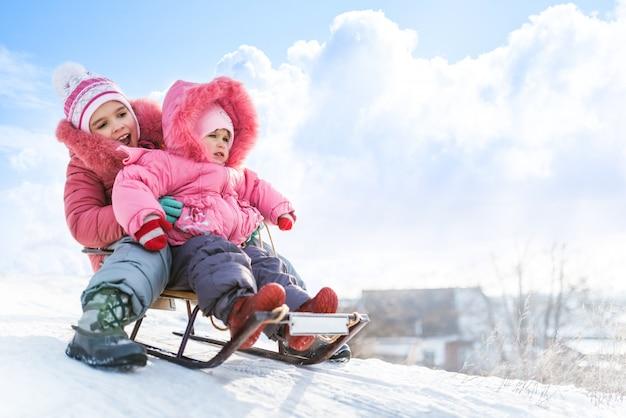 Felizes meninas pequenas em roupas de inverno rosa trenó ladeira abaixo na neve