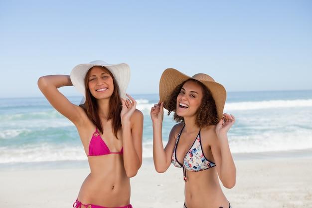 Felizes mulheres jovens em pé na praia ao lado