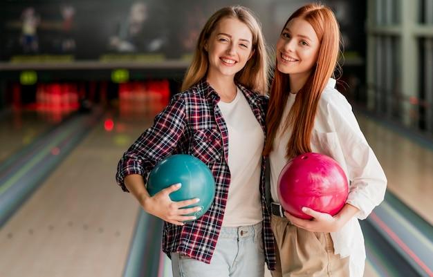 Felizes mulheres jovens posando em um clube de boliche