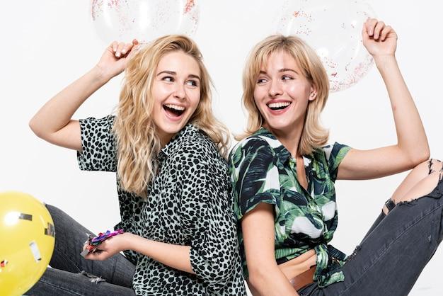 Felizes mulheres loiras segurando confetes