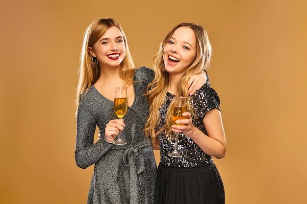 Felizes mulheres sorridentes em elegantes vestidos glamourosos com taças de champanhe na parede dourada