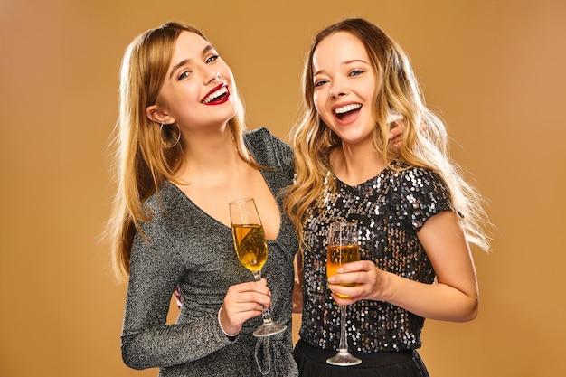 Felizes mulheres sorridentes em elegantes vestidos glamourosos com taças de champanhe